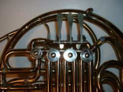 The valves of a Conn 6D double horn. The 3 lever keys (above the large valves) can be depressed toward the large outer tube. The thumb key (near the left-most valve) moves inward toward the 3 finger keys.